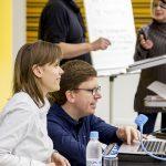 Im Vodergrund richtet Orgamitglied Stefan Farnetani gemeinsam mit Referentin Franziska Sgoff ihren Computer mit Braillezeile ein. Im Hintergrund unterhält sich das Orgateam des WUDs.