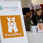 Roll Up des WUDs mit Logo des World Usability Days, das Logo des WUDs München (abstrakte Lederhose) und dem Hashtag #wudmuc. Im Hintergrund der Anmeldethresen mit dem Orgateam.