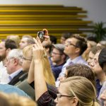 Teilnehmerin im Publikum fotografiert.