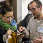 Thomas Heilmann zeigt Teilnehmerin an ihrem Smartphone, wie sehbehinderte und blinde Menschen Smartphones verwenden.